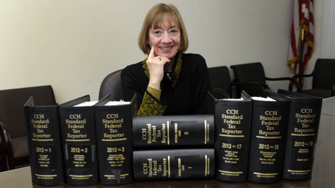 "In this Thursday, Jan. 9, 2014 photo, National Taxpayer Advocate Nina Olson poses with tax code books at the Internal Revenue Service in Washington. Olson says it's not too early to start thinking about the tax implications of health care reform. ""We have an opportunity in the 2014 filing season to educate taxpayers about what they need to do during the year to avoid problems during the 2015 filing season,"" Olson said in a wide-ranging interview. (AP Photo/Susan Walsh)"