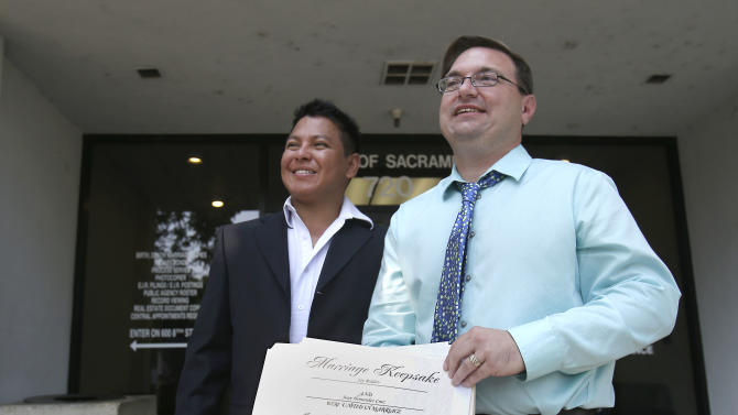"Juan Carlos Hernandez, left, and Jay Redden, smile as they talk with reporters outside the Sacramento County Recorder's office were they had just gotten married, in Sacramento, Calif., Monday, July 1, 2013. A three-judge panel of the 9th U.S. Circuit Court of Appeals issued a brief order Friday afternoon dissolving, ""effective immediately,"" a stay it imposed on gay marriages while the lawsuit challenging the ban advanced through the court. (AP Photo/Rich Pedroncelli)"
