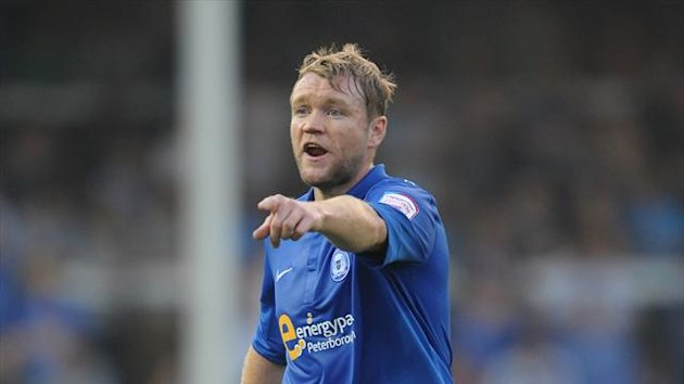 Grant McCann's penalty 11 minutes from time rescued a point for Peterborough