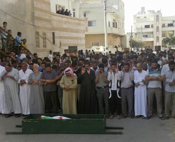 This citizen journalism image released by Shaam News Network taken Sunday, July 1, 2012 purports to show people praying during the funeral of Zahar Radwan Ibrahim Massalmeh who was killed in fighting with Syrian government forces in Daraa, Syria. (AP Photo/Shaam News Network)THE ASSOCIATED PRESS IS UNABLE TO INDEPENDENTLY VERIFY THE AUTHENTICITY, CONTENT, LOCATION OR DATE OF THIS CITIZEN JOURNALISM IMAGE