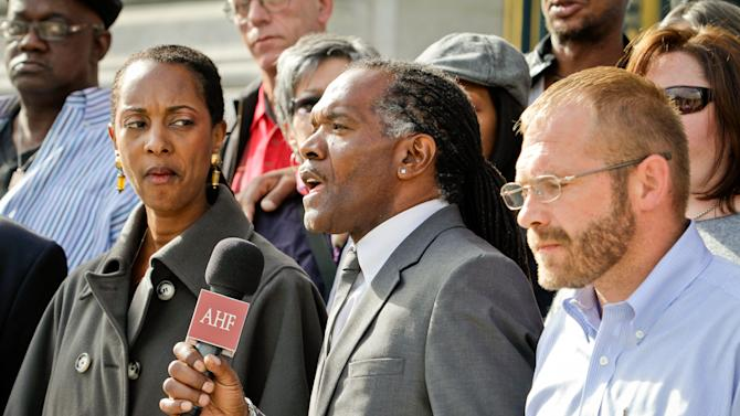 IMAGE DISTRIBUTED FOR AIDS HEALTHCARE FOUNDATION - AHF's Dr. Lisha Wilson and Dale Gluth flank community activist and ballot measure proponent Jesse Brooks as he speaks at a press conference to announce the launch of a new ballot initiative to rein in drug pricing on the steps of San Francisco City Hall on Thurs., Nov. 15, 2012 in San Francisco. (John Storey/AP Images for AIDS Healthcare Foundation)