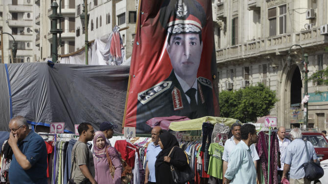 Egyptians walk past a banner with a portrait of Egyptian Presidential hopeful Abdel-Fattah el-Sissi at a market in Cairo, Egypt, Saturday, May 17, 2014. El-Sissi faces leftist Hamdeen Sabahi, who has the support of youth groups who led the 2011 uprising against autocrat Hosni Mubarak. El-Sissi, who led the July 3, 2013 overthrow after millions protested against Islamist President Mohammed Morsi, is widely expected to win the May 26-27 vote on a wave of nationalistic, anti-Islamist fervor. (AP Photo/Amr Nabil)