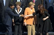 Bolivia's President Evo Morales (L) shakes hands with Argentina's President Cristina Fernandez de Kirchner, in front of Brazil's President Dilma Rousseff (2nd L) and German Chancellor Angela Merkel before the official picture of the Community of Latin American and Caribbean States-European Union Summit, on January 26, 2013.