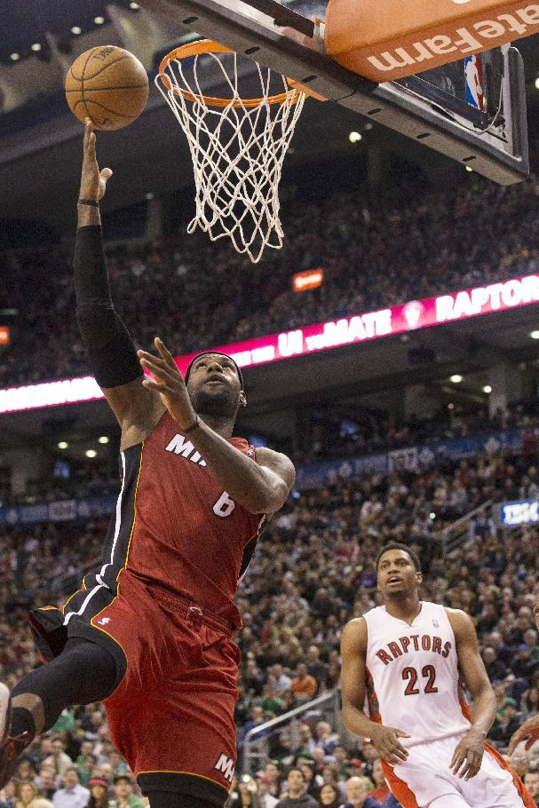 Miami Heat's LeBron James, left,  jumps for the net as Toronto Raptors' Rudy Gay looks on during second half NBA basketball action in Toronto on Sunday March 17, 2013.  (AP Photo/The Canadian Press, Chris Young)
