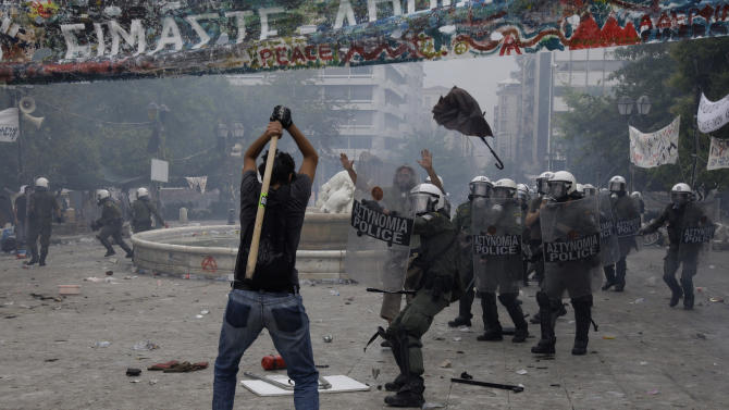 FILE-In this  Wednesday, June 29, 2011 file photo, a protester hits out with a stick against riot policemen during clashes at Athens' main Syntagma square. In the midst of Greece's acute financial crisis, the company rents communal space to tech-savvy startups on the theory that the more they mingle, the more they thrive. The concept runs against a trend that has left many of Greece's brightest minds feeling their only choice is to emigrate, anticipating a domestic opportunity drought for a decade.  (AP Photo/Petros Giannakouris, FILE)