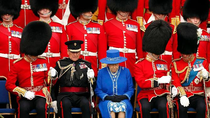 Queen Elizabeth (C), Prince Philip (2L), and Prince Charles (R), prepare to pose for a regimental photograph at Windsor Castle, April 30, 2015