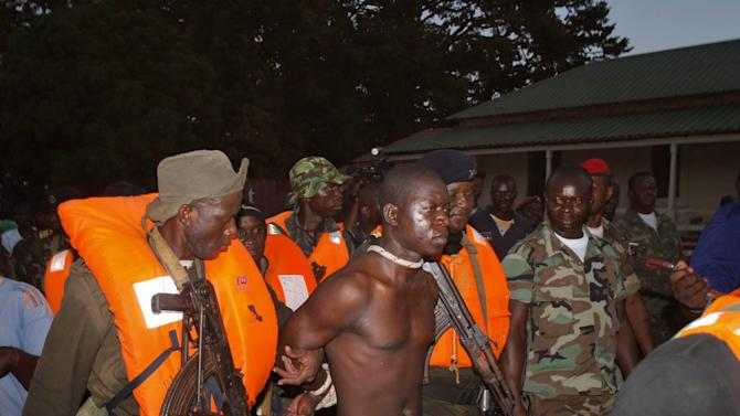 In this Saturday, Oct. 27, 2012 photo, Pansau Ntchama, center, accused of leading a failed Oct. 21 coup attempt, is restrained by soldiers as he is brought to Bissau, Guinea-Bissau, following his arrest. Gunmen led by Ntchama allegedly attacked a military base near the airport in Bissau last week, and six soldiers were killed in the clash. The apparent attempted coup was against the military junta that itself seized power in April.(AP Photo)