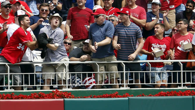 The fans and San Francisco Giants left fielder Ryan Lollis can't catch a solo home run by Washington Nationals' Michael Taylor during the first inning of a baseball game at Nationals Park, Saturday, July 4, 2015, in Washington. (AP Photo/Alex Brandon)