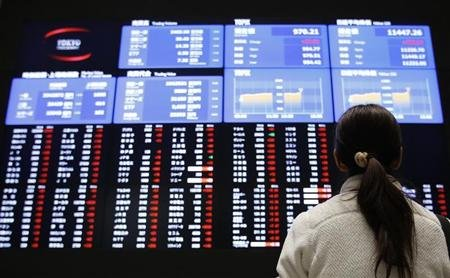 A woman looks at an electronic board showing Japan's stock price index at the Tokyo Stock Exchange in Tokyo