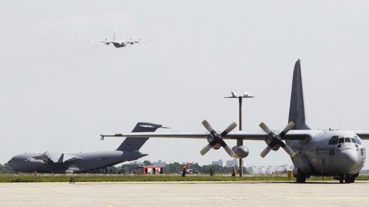 A Hercules transport aircraft of the Royal Dutch Airforce and a Royal Australian Air Force Boeing C-17 are seen at an air-strip before transporting some of the remains of the victims of the downed Malaysia Airlines Flight MH17 airliner at Kharkiv airport