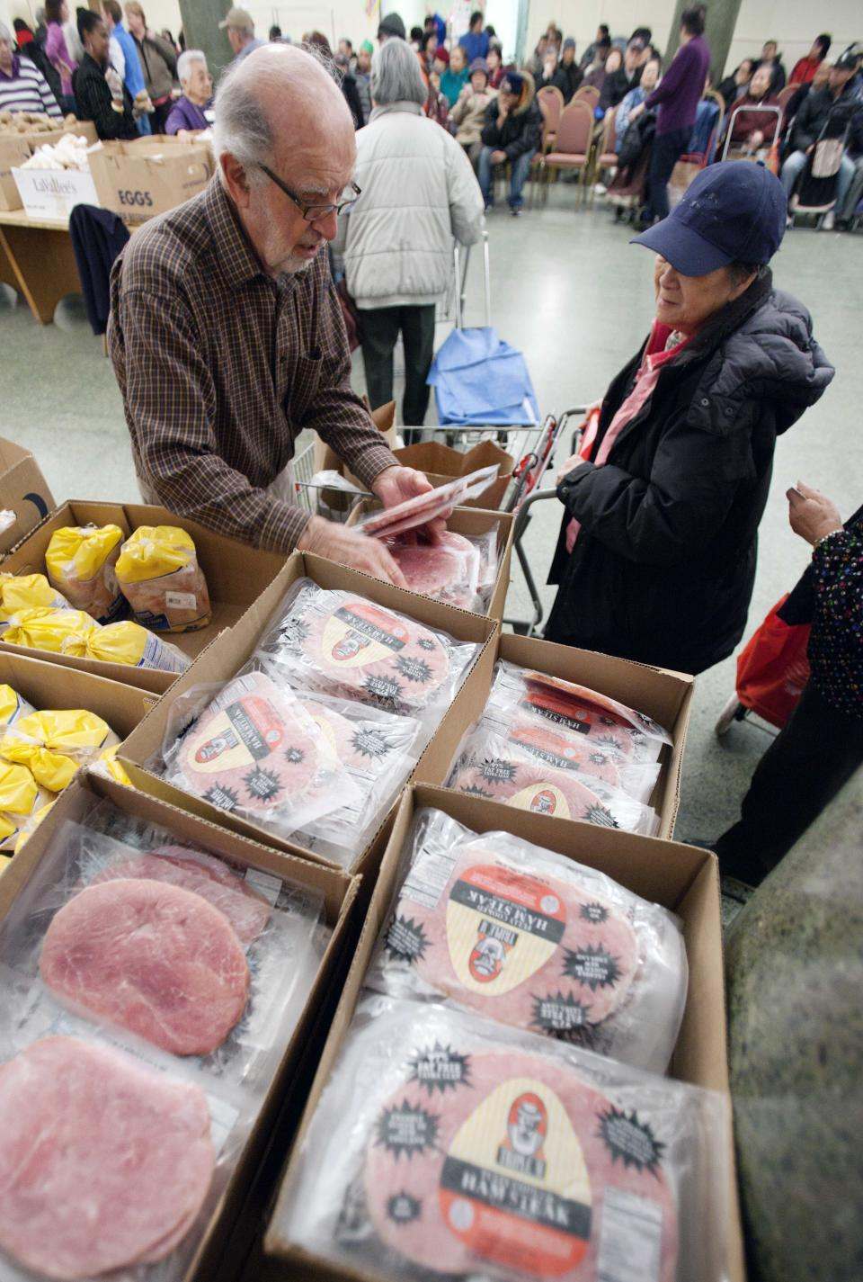 In this Thursday, March 29, 2012 photo, Paul Farris, left, of Boston, distributes hams in the Franciscan Food Center food pantry at St. Anthony Shrine in Boston. Ham prices have been higher than usual for the past two years because the cost of pig feed has gone up. (AP Photo/Michael Dwyer)