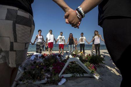 People hold hands as they pray in a circle around bouquets of flowers laid as mementos on the beach of the Imperial Marhaba resort, which was attacked by a gunman, in Sousse, Tunisia