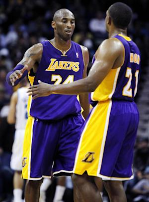 Los Angeles Lakers shooting guard Kobe Bryant (24) is greeted by point guard Chris Duhon (21) at the end of the first half of an NBA basketball game against the New Orleans Hornets in New Orleans, Wednesday, Dec. 5, 2012. Bryant became the youngest player in NBA history to break 30,000 points during the half. (AP Photo/Gerald Herbert)