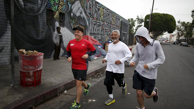 Runners from the Midnight Mission Running Club, Tom Cohen, Oscar Knight, 53, and Seth Becker, 22, run through Skid Row in Los Angeles