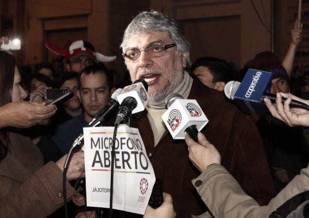 "FILE - In this June 24, 2012 file photo, Paraguay's former President Fernando Lugo talks through the ""open microphone"" of the Public Television, surrounded by reporters and followers in downtown Asunc"