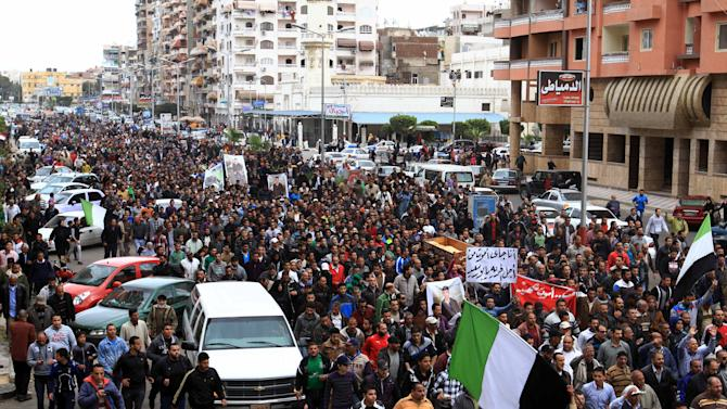 Thousands of residents, several waving a black-white-and-green flag of Port Said, that has become a symbol of the city's revolt against the government, join a funeral procession for civilians killed overnight during street battles with police forces, in Port Said, Egypt, Monday, March 4, 2013. The fighting on Sunday prompted the military to intervene to break up the clashes, the first such intervention by the army since the military was deployed in Port Said in late January when tension between protesters and police first erupted. (AP Photo/Ahmed Ramadan)