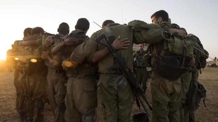 Israeli soldiers stand in a circle at a staging area before entering Gaza from Israel
