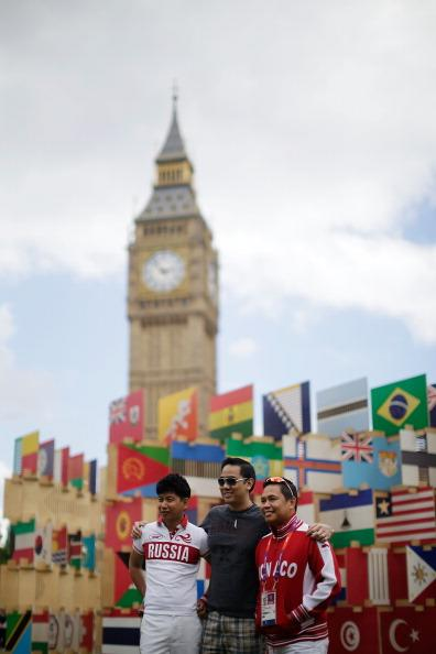 Tourists take pictures in front of The House of Flags installation in Parliament Square on August 2, 2012 in London, England. 206 panels displaying all the flags of the nations participating in the 2012 Olympics and Paralympics, have been combined together into a jigsaw 'house'. (Photo by Matthew Lloyd/Getty Images)