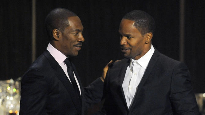 """Eddie Murphy, left, is greeted onstage by actor/comedian Jamie Foxx at """"Eddie Murphy: One Night Only,"""" a celebration of Murphy's career at the Saban Theater on Saturday, Nov. 3, 2012, in Beverly Hills, Calif. Murphy and Foxx were cast members in the 2006 film """"Dreamgirls."""" (Photo by Chris Pizzello/Invision)"""