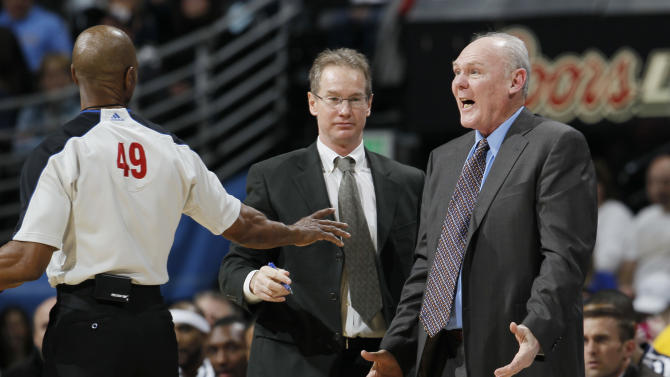 Denver Nuggets coach George Karl, right, argues a call against his team with referee Tom Washington, left, as assistant coach John Welch intervenes as the Nuggets played the Sacramento Kings in the first quarter of an NBA basketball game in Denver on Saturday, March 23, 2013. (AP Photo/David Zalubowski)