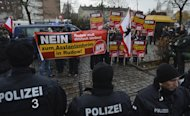 Policemen stand in front of supporters of German far-right party NPD (National Democratic Party of Germany) during a demonstration in Berlin on November 24, 2012. The Philippine government said it would never share power with communist rebels after they proposed an alliance in a bid to end a decades-long insurgency