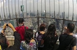 Visitors stand on the observation deck of the Empire State building in New York