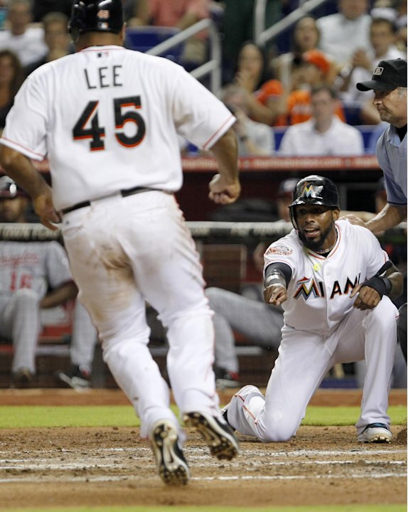 Miami Marlins' Jose Reyes yells to Carlos Lee (45) as he heads home during the third inning of a baseball game against the Washington Nationals, Tuesday, Aug. 28, 2012, in Miami. Both Reyes and Lee sc