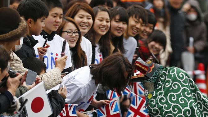 Children in a lion costume pretend to bite the head of a woman as people wait for the arrival of Britain's Prince William in Onagawa
