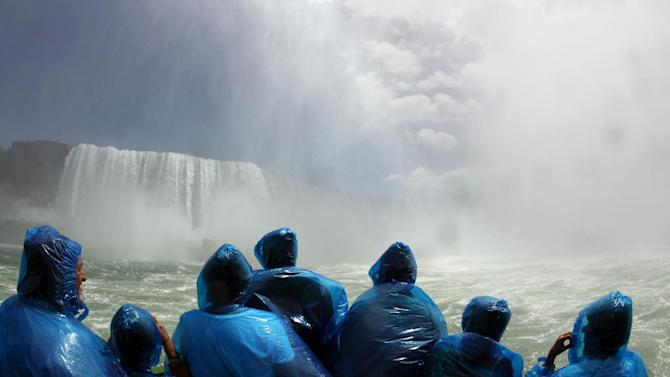 FILE - In this June 11, 2010 file photo, tourists ride the Maid of the Mist boat at the base of the Horseshoe Falls in Niagara Falls, N.Y. The tour company chosen to take over the Niagara Falls tour boat business in Canada says it plans to build customized new boats and upgrade amenities while maintaining the things that have made the sightseeing rides so popular for more than 100 years. (AP Photo/David Duprey, File)