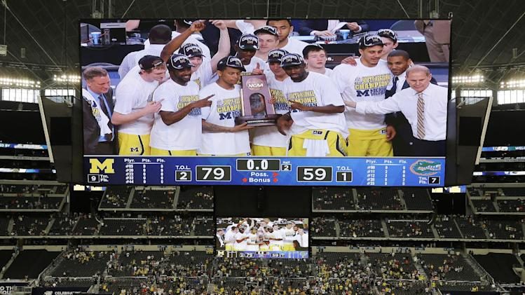 Michigan celebrates with the trophy after a regional final game against Florida in the NCAA college basketball tournament, Sunday, March 31, 2013, in Arlington, Texas. Michigan won 79-59 to advance to the Final Four. (AP Photo/David J. Phillip)