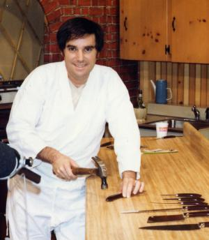 "In this 1978 photo made available by PriMedia shows Barry Becher at a studio using a hammer on a Ginsu knife. Becher, a marketing mastermind and infomercial pioneer best know for bringing Ginsu knives to the American public, died of complications from surgery. He was 71. Becher was buried in Tamarac, Fla., on Monday, June 25, 2012. His family is considering etching in his tombstone one of the carchphrases he help popularize: ""But wait, there's more."" (AP Photo/PriMedia)"
