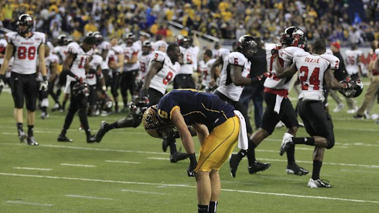 Kent State wide receiver Chris Humphrey (6) lowers his head as the Northern Illinois team celebrate their 44-37 win in the second overtime of the Mid-American Conference championship NCAA college football game on Friday, Nov. 30, 2012. (AP Photo/Carlos Osorio)