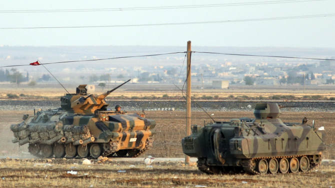 Turkish forces on armoured vehicles at the outskirts of Suruc, secure the border area with Syria, background, Monday, Oct. 6, 2014. Kobani, also known as Ayn Arab and its surrounding areas have been under attack since mid-September, with militants capturing dozens of nearby Kurdish villages. The flag is indicating that the jihadists may have regrouped and broken through the Kurdish lines. (AP Photo/Lefteris Pitarakis)