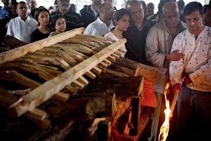 Ramesh Vaya, right, lights the funeral pyre of his …