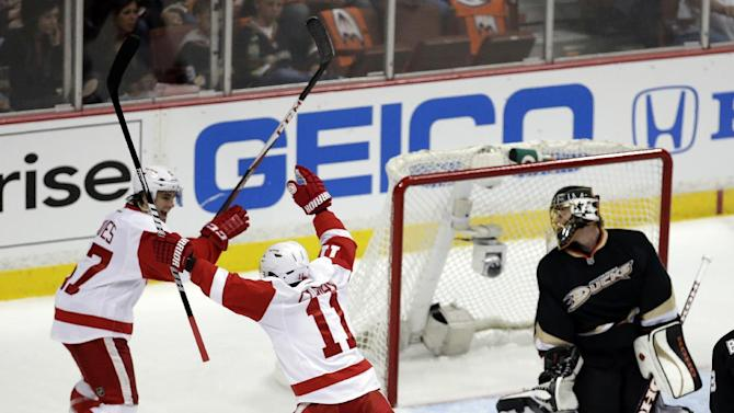 Detroit Red Wings right wing Daniel Cleary, middle, celebrates his goal past Anaheim Ducks goalie Jonas Hiller, right, with Patrick Eaves during the first period in Game 1 of their first-round NHL hockey Stanley Cup playoff series in Anaheim, Calif., Tuesday, April 30, 2013. (AP Photo/Chris Carlson)
