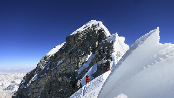 In this May 18, 2013 photo released by mountain guide Adrian Ballinger of Alpenglow Expeditions, climbers navigate the knife-edge ridge just below the Hillary Step on their way to the summit of Mount Everest, in the Khumbu region of the Nepal Himalayas. Guy Cotter was so concerned about the safety of Sherpa guides and porters through Mount Everest's notorious Khumbu Icefall that he and another commercial guide operator hatched a plan: Before this year's climbing season began, they would use helicopters to transport four tons of equipment above the icefall. Nepal-based Simrik Air backed the plan and hired New Zealand pilot Jason Laing, an expert in hauling loads using long cables. But in January, the answer came back from Nepalese authorities: permit denied. Three months later, Laing put his expertise to use. But not hauling gear. On April 18 came Everest's worst disaster, in which 16 Sherpas were killed in an avalanche at the icefall. Laing made flight after flight that day, using his long cables to rescue four injured Sherpas and haul out 13 bodies. (AP Photo/Alpenglow Expeditions, Adrian Ballinger) MANDATORY CREDIT, EDITORIAL USE ONLY