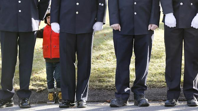 A child peers through firefighters standing as the procession heads to the cemetery outside the funeral for school shooting victim Daniel Gerard Barden at St. Rose of Lima Catholic Church in Newtown, Conn., Wednesday, Dec. 19, 2012. According to firefighters, Daniel wanted to be a firefighter when he grew up and they honored him at the service. Barden, 7, was killed when Adam Lanza walked into Sandy Hook Elementary School in Newtown, Conn., Dec. 14, and opened fire, killing 26 people, including 20 children, before killing himself. (AP Photo/Charles Krupa)