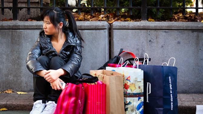 A consumer rests herself and her bags in Herald Square during the busiest shopping day of the year, Friday, Nov. 25, 2011, in New York. Some of the nation's major chain stores opened late Thursday, competing for holiday shoppers on the notoriously busy Black Friday to kick off a period that is crucial for the retail industry. (AP Photo/John Minchillo)