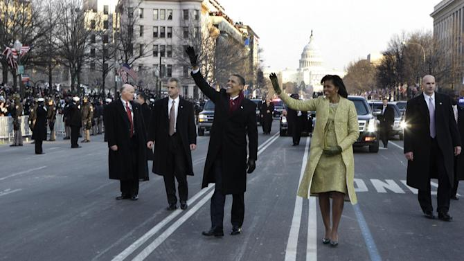 FILE - This Jan. 20, 2009 file-pool, photo shows President Barack Obama and first lady Michelle Obama waving as they walk down Pennsylvania Avenue en route to the White House from the Capitol in Washington. At some point on Inauguration Day, if all goes expected, the president's limousine will slow to a stop on its journey down Pennsylvania Avenue from the Capitol to the White House. A Secret Service agent will open the rear passenger door, and the newly sworn-in president will emerge from his car for a several-minute stroll. The crowd will cheer. The president will wave. In that moment, Pennsylvania Avenue is America's red carpet. And the president is the only celebrity on it. The victory walk has become an iconic inaugural moment, one expected by the public and the press.  And though the tradition dates only to President Jimmy Carter, it has already developed an air of inevitability and predictable patterns.   (AP Photo/Doug Mills, File, Pool)