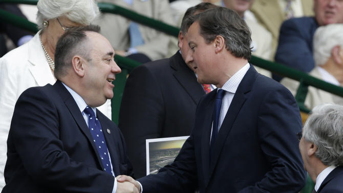 FILE - In this Sunday, July 8, 2012 file photo, Britain's Prime Minister David Cameron, right, shakes hands with Scottish First Minister Alex Salmond ahead of the men's final match at the All England Lawn Tennis Championships at Wimbledon, England between Roger Federer of Switzerland and Andy Murray of Britain. The British prime minister is due to visit the leader of Scotland's separatist administration on Monday Oct. 15, 2012 to agree the terms of a referendum that could break up the United Kingdom. Cameron does not want to be the leader who presides over the demise of the 300-year-old political union between England and its northern neighbor. But, practically, there is little he can do to stop politicians in semiautonomous Scotland asking voters whether they want to break free. (AP Photo/Kirsty Wigglesworth, File)