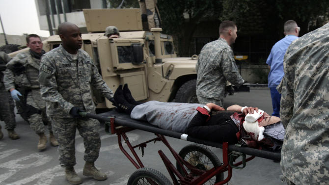 """In this Saturday, Dec. 16, 2007 photo, U.S. Army medical staff rush an Iraqi woman who was shot in the face by U.S. troops in an """"escalation of force"""" incident, to the emergency room at Ibn Sina Hospital in the Green Zone in Baghdad, Iraq. Military documents in the biggest leak of secret information in U.S. history suggest that far more Iraqis died than previously acknowledged during the years of sectarian bloodletting and criminal violence unleashed by the 2003 U.S.-led invasion. The 391,831 documents date from the start of 2004 to Jan. 1, 2010, providing a ground-level view of the war written mostly by low-ranking officers in the field. The dry reports, full of military jargon and acronyms, were meant to catalog """"significant actions"""" over six years of heavy U.S. and allied military presence in Iraq.(AP Photo/Maya Alleruzzo)"""