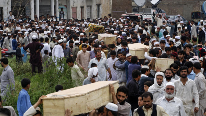 Pakistani villagers carry coffins of victims killed from heavy rain and windstorm that reached up to a speed of 120 kph (75 mph) Sunday evening which collapsed hundreds of buildings, uprooted trees, and electric poles, in Peshawar, Pakistan, Monday, April 27, 2015. Officials say death toll has risen to at least 44. (AP Photo/Mohammad Sajjad)