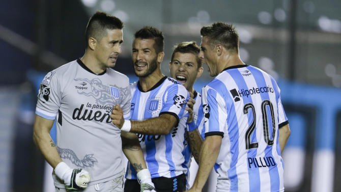 Nelson Ibanez of Argentina's Racing Club, left, is congratulated by teammates German Voboril, second left, Leandro Grimi, second right, and Ivan Pillud after stopping a penalty shot by Julian Benitez of Paraguay's Guarani during a Copa Libertadores quarter finals soccer match in Buenos Aires, Argentina, Thursday, May 28, 2015. (AP Photo/Natacha Pisarenko)
