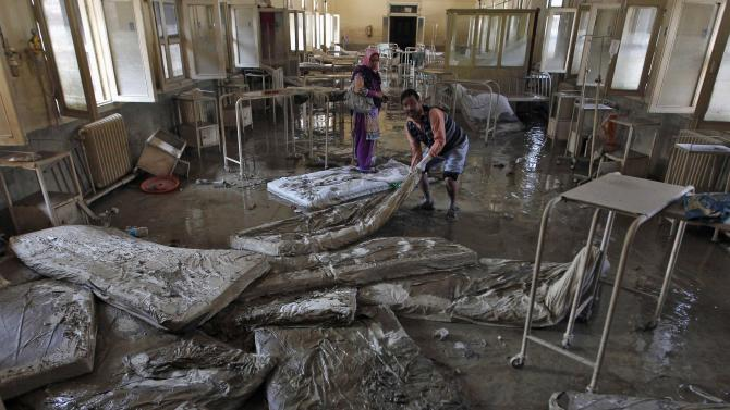 A man removes muddied beddings from a hospital ward which was damaged by flooding in Srinagar