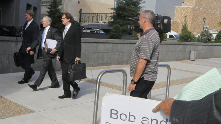 Former Virginia Gov. Bob McDonnell , second from left, arrives at federal court with his attorneys John Brownlee, left, and Henry Asbill, third from left, as a demonstrator holds a sign in Richmond, Va., Wednesday, Aug. 20, 2014. The defense continues to present it's case in the McDonnell corruption trial. (AP Photo/Steve Helber)