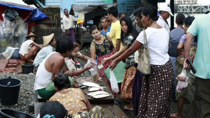Locals buy fish from roadside vendors in Sittwe, the capital of Rakhine state in western Myanmar, where sectarian violence continues to impact the public, Wednesday, June 13, 2012. Heavy rain Wednesday brought an uneasy calm to western Myanmar after five days of deadly sectarian strife, though residents said they were too afraid to sleep at night and faced food shortages. (AP Photo/Khin Maung Win)