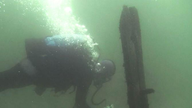 In this October 2012 image from video provided by David J. Ruck, diver Tom Kucharsky passes timbers protruding from the bottom of Lake Michigan that were discovered by Steve Libert, head of Great Lakes Exploration Group, in 2001. On Saturday, June 15, 2013, Libert will lead a diving expedition to an underwater site in northern Lake Michigan, where archaeologists and technicians will try to determine whether the timbers and other items beneath layers of sediment are what remain of 17th Century French explorer La Salle's legendary Griffin. (AP Photo/David J. Ruck ) MANDATORY CREDIT