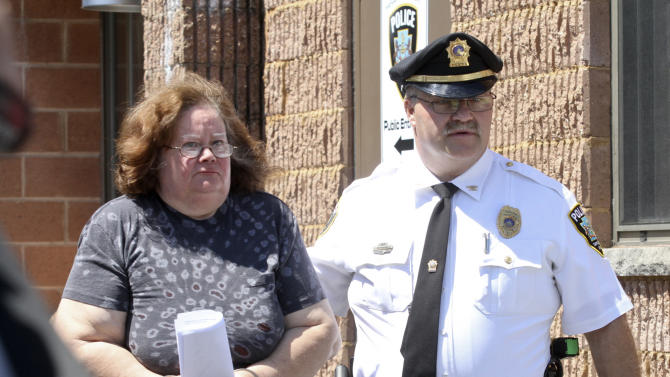 CORRECTS TO CLARIFY CHARGES Susan Gensiak, 59, of Taylor, Pa., is lead by a police officer to arraignment, Wednesday, June 19, 2013 in Scranton, Pa. Gensiak and her two daughters have been charged with third-degree murder, involuntary manslaughter and neglect of care for a dependent person. (AP Photo/Scranton Times & Tribune, Michael J. Mullen) WILKES BARRE TIMES-LEADER OUT; MANDATORY CREDIT