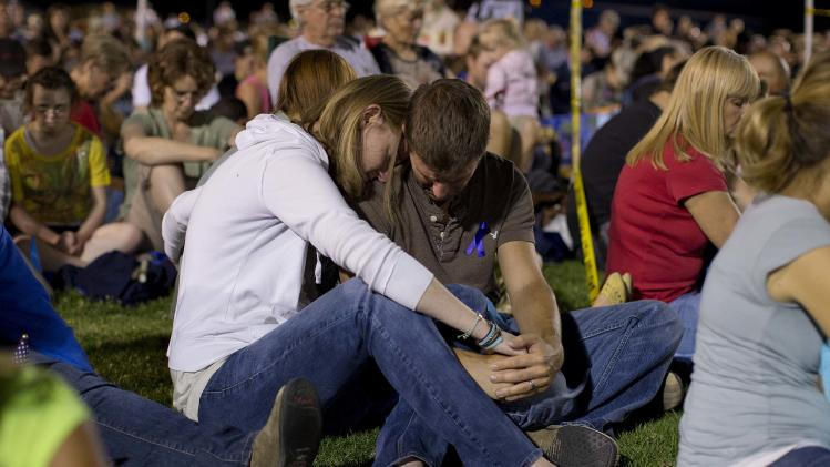 A couple bows their head in prayer during a candlelight vigil in Prescott, Ariz. on Tuesday, July 2, 2013 to honor the 19 Granite Mountain Hotshot firefighters who were killed by an out-of-control blaze near Yarnell, Ariz. on Sunday. (AP Photo/Julie Jacobson)