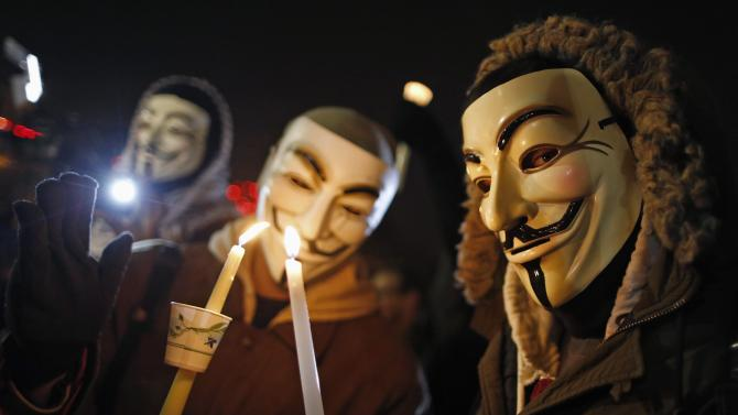 Protesters wearing Guy Fawkes masks take part in a candlelight vigil outside the Ferguson Police Department in Ferguson